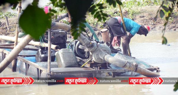কুমিল্লায় ডাকাতিয়া নদী থেকে ড্রেজার মেশিন দিয়ে অবৈধভাবে বালু উত্তোনল