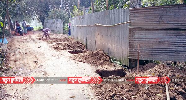 কুমিল্লায় এলজিইডি সড়কে বাড়ির সীমানা প্রাচীর নির্মাণ